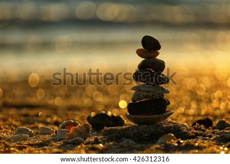 Balancing stones stacked on top of each other at sunset, spa concept  - stock photo