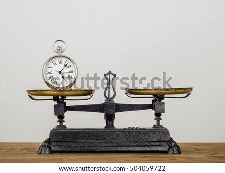 Balancing time. Old pocket watch on Antique vintage balance scales, Cast iron and brass.