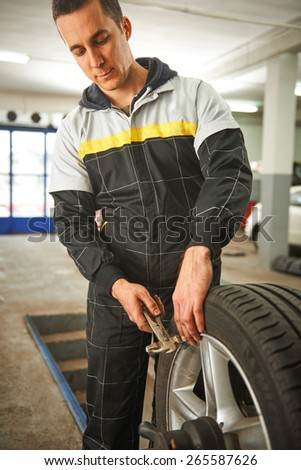 Balancing tire in car service - stock photo