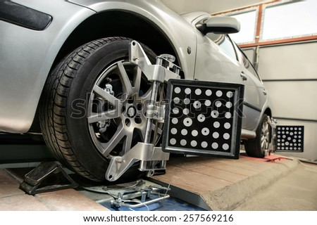 Balancing wheels on the car to the service station - stock photo
