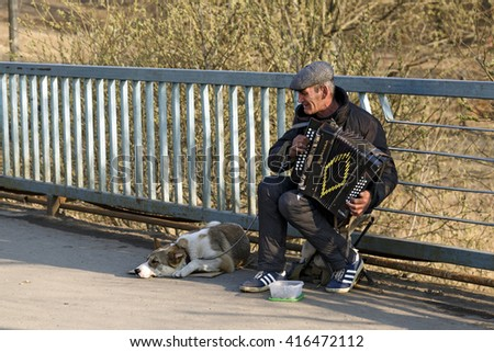 BALASHIKHA, RUSSIA - APRIL, 13. Street musician playing the accordion, with the dog on the bridge on April 13, 2014 in city Balashikha, Moscow region.