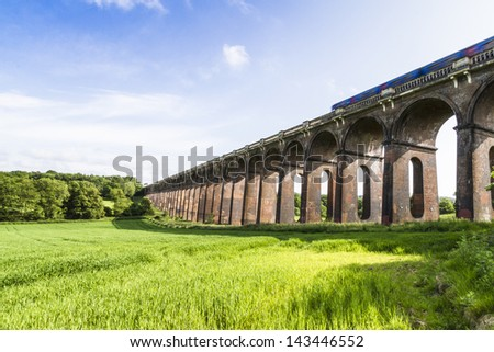 Balcombe Ouse Valley Viaduct designed by John Urpeth Rastrick for the London and Brighton Railway and completed in 1842 comprising 37 arches. Sussex England. Motion blurred train crossing at speed - stock photo