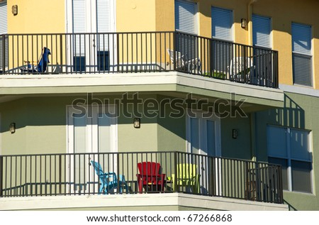 Balconies in pastel colors in bright sunlight with colorful chairs. - stock photo