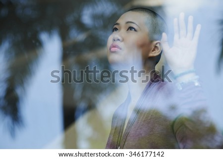 Bald beautiful woman looking through the window with hope - stock photo