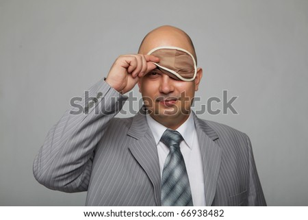 Bald businessman in a gray suit with a gray background with a bandage to sleep in his eyes
