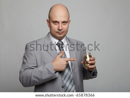 Bald businessman in a gray suit with a gray background with a can with coins in hand - stock photo