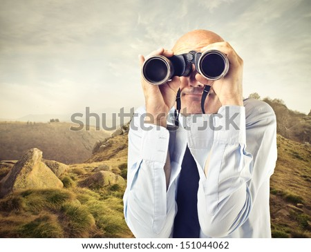 bald businessman looking with binoculars to the horizon - stock photo