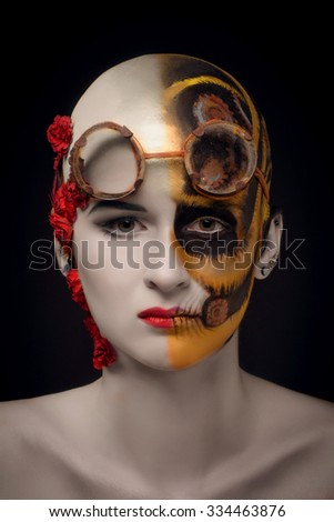 Bald girl with a art make up and steampunk glasses, on the one hand a mechanical robot, on the other blooming desert - stock photo