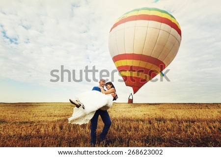 bald groom holds a brunette bride on background balloon and cloudy sky