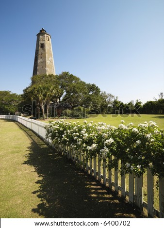 Bald Head Lighthouse with fence and wild roses at Bald Head Island, North Carolina. - stock photo