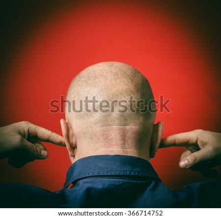 Bald man covered his ears with his fingers - stock photo