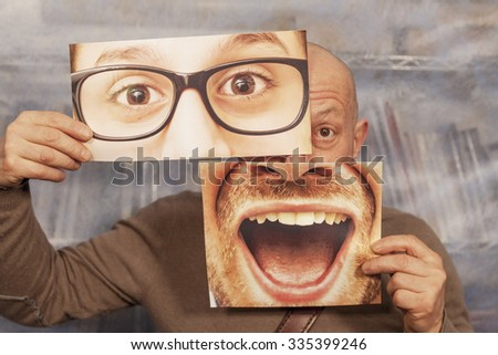 bald man holding a card with a big smile and big glasses on it - stock photo