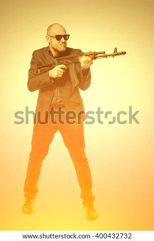 Bald man in a gray suit and sunglasses holding a machine gun in his hands. Toned