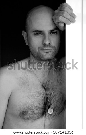 bald man leaning out of the window with nude torso - stock photo