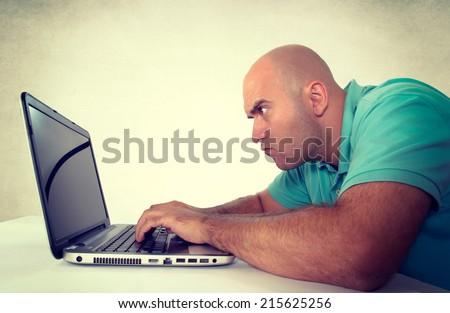 Bald man looking at the laptop computer - stock photo