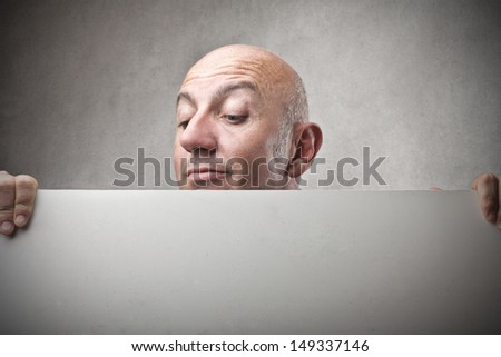 bald man looking down on billboard - stock photo
