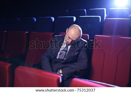 Bald man sleeping in empty movie theater. - stock photo
