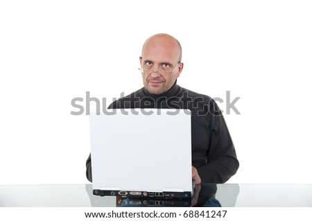 Bald man with reading glasses working with his laptop - stock photo
