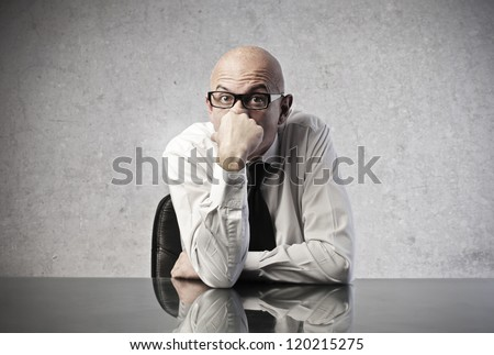 Bald office worker reflecting with a hand over her mouth