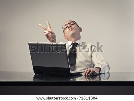 Bald satisfied businessman making a victory sign - stock photo