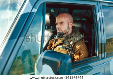 Bald soldier in uniform is driving military vehicle. - stock photo