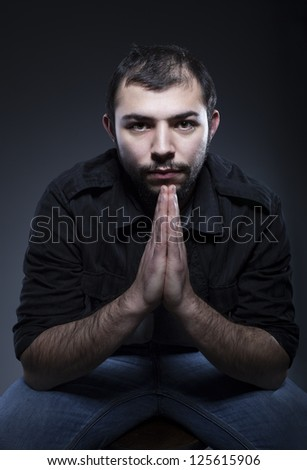 balding man with hands together looking at camera on dark background - stock photo