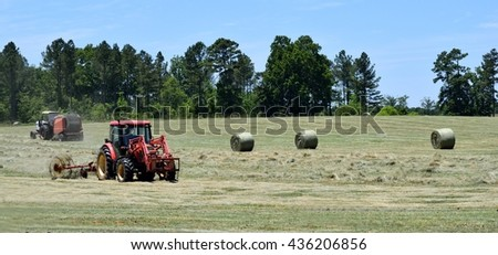 Bales of hay being baled by tractors background - stock photo