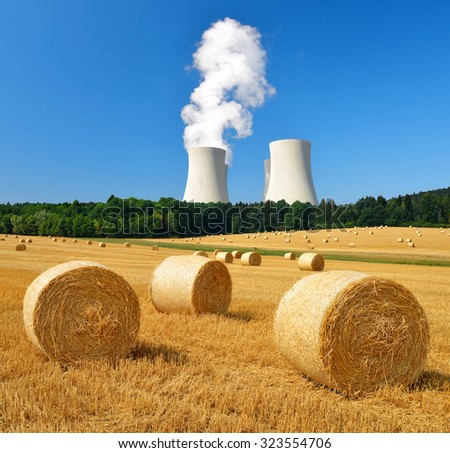 Bales of straw on the field in the background cooling tower nuclear power plant - stock photo