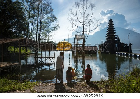 BALI - APRIL 11, 2014: Balinese Hindu devotees go to pray at an ancient temple on Lake Batur, a volcano crater lake in Bali, Indonesia. Religious rituals and ceremonies are a way of life in Bali. - stock photo
