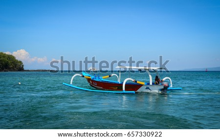 Bali, Indonesia - Apr 19, 2016. Traditional boat runs on sea in Bali Island, Indonesia. Bali is part of the Coral Triangle, the area with the highest biodiversity of marine species.