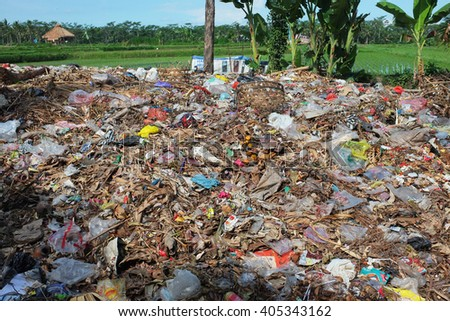 BALI, INDONESIA - April 10, 2016: Illegally-dumped garbage and plastic bags contaminate agricultural land at a waste-recycling center in Pejeng on April 10, 2016 in Ubud, Bali, Indonesia. - stock photo