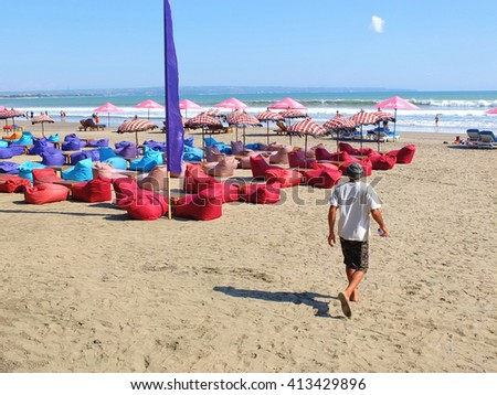 BALI, INDONESIA - APRIL 28, 2016: Tourist walking on beach with Bean bags, umbrellas and sun beds, Seminyak, Bali, Indonesia.