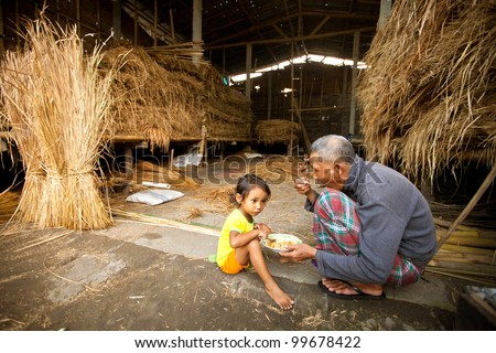 BALI, INDONESIA - APRIL 3: Unidentified poor child eats with his father during a break working on the farm  on Apr 3, 2012 on Bali. Daily caloric intake per capita in Indonesia is 2891 kcal per person - stock photo