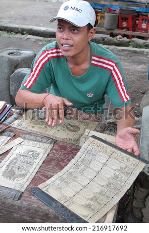 BALI, INDONESIA, AUGUST 16, 2014 : A young man shows traditional calendars to tourists in Tenengan village, one of last traditional Bali Aga community.