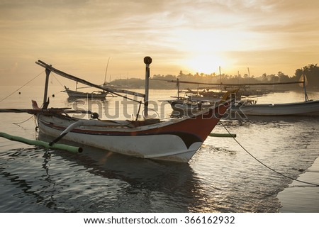 Bali, Indonesia. Fishing boats populate the shoreline in the small fishing village of Pemuteran in the northwest corner of Bali, Indonesia. Beautiful sunrises are common along the coast. - stock photo