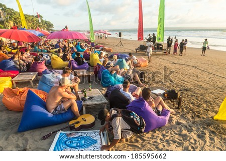 Bali, Indonesia - January 9 2014: A large crowd of people enjoy drinks at a beach bar directly on Seminyak beach before sunset in Bali. - stock photo