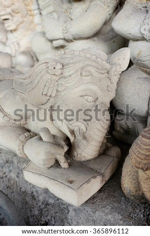 BALI, INDONESIA - January 22, 2016: The hand-carved statue of the Hindu Elephant God of Learning, Ganesh, writes in a book at a stone-carver's workshop on January 22, 2016 in Ubud, Bali, Indonesia.