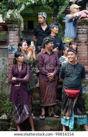 BALI, INDONESIA, JULY 14: unidentified balinese people and one tourist during the cremation ceremony in Penestanan, Bali on July 14th 2010. - stock photo