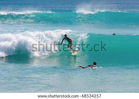 BALI, INDONESIA - JULY 27: Unidentified young man surfs the waves on July 27, 2010. Dreamland beach, Bali, Indonesia. The Dreamland is one of the most popular surfing areas of Bali. - stock photo