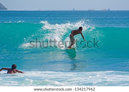 BALI, INDONESIA - JULY 27: Unidentified young men surfing the waves on July 27, 2010. Dreamland beach, Bali, Indonesia. The Dreamland is one of the most popular surfing areas of Bali. - stock photo