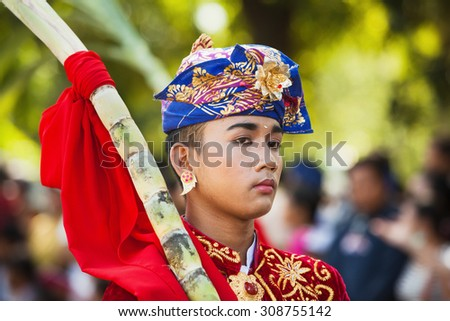 BALI, INDONESIA - JUNE 13: Portrait of Bali man in beautiful Balinese people costume with traditional style face make-up on parade at Bali arts and culture festival in Denpasar, Bali, 13 June, 2015 - stock photo