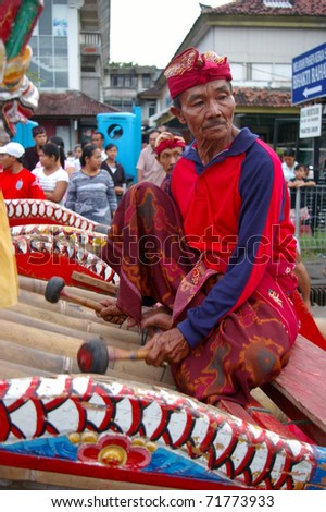 BALI, INDONESIA - MARCH 7: Gamelan player participates in the annual Balinese festival of Pengrupukan, March 7, 2008, Denpasar, Bali. This celebrates the Balinese New Year and the arrival of spring. - stock photo
