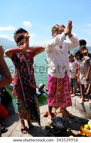 BALI, INDONESIA - November 16, 2012: A young Balinese couple perform Hindu marriage rituals next to Lake Batur on November 16, 2012 in Trunyan Village, Kintamani, Bali, Indonesia.