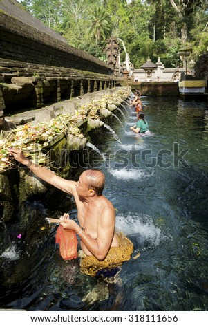 Bali, Indonesia, September 09, 2014 : Balinese people praying at holy spring water at Pura Tirtha Empul temple during religious ceremony in Tampak Siring, Bali, Indonesia.  - stock photo