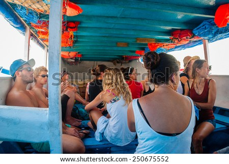 BALI, INDONESIA - SEPTEMBER 25: Group of young travellers travelling on public boat from Bali to Nusa. Indonesian public boats are usually crowded. Taken on Bali, Indonesia on September 25, 2014 - stock photo