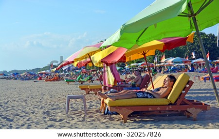 Bali, Indonesia - September13, 2015: Tourists Snooze on colourful recliner chairs at Legian Beach in the afternoon. - stock photo