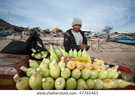 BALI - JANUARY 16: Life in a fishing village, trader sells steamed corn on the beach at Jimbaran village, Bali January 16, 2010 in Bali, Indonesia. - stock photo