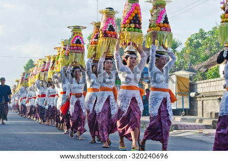 BALI - JUNE 25: Village women carry offerings of food baskets on their heads in a procession to the village temple June 25, 2012 in Bali, Indonesia.