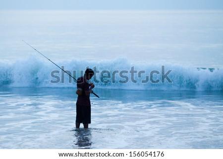BALI - MARCH 11: Balinese man goes fishing on the beach on March 11, 2012 in Jimbaran beach Bali.  - stock photo