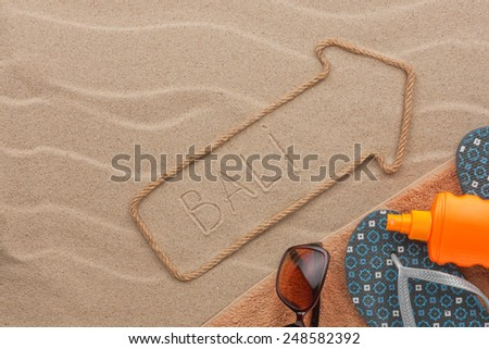 Bali pointer and beach accessories lying on the sand, as background - stock photo